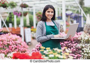 mujer, Utilizar, computador portatil, jardín, centro