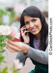 Smiling florist touching a flower and making a call -...