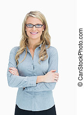 Woman with glasses crossing her arms while smiling