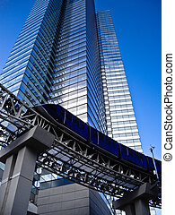 Monorail at foot of tall modern Building - Monorail gliding...
