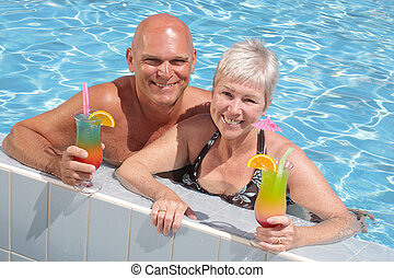couple in the pool - attractive couple relaxing by the pool