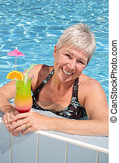 woman in swimming pool - attractive mature woman relaxing by...
