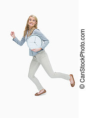 Woman running while holding a clock - Hurried woman running...