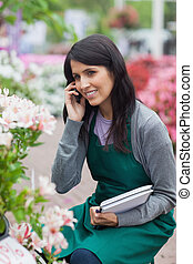 Employee doing stocktaking while calling in garden center -...