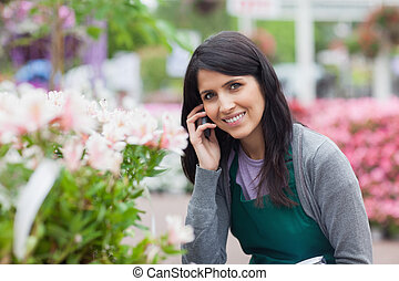 Smiling florist outside the garden centre - Smiling florist...