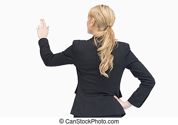 Standing businesswoman pointing som - Businesswoman pointing...