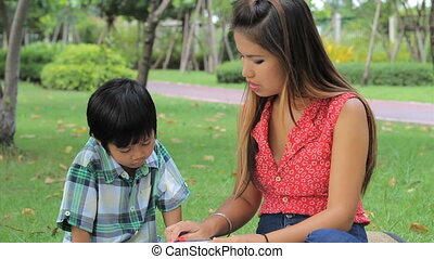 Asian Mom Teaching Son To Read - A pretty Thai mother...