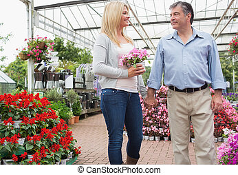 Couple strolling through garden center - Couple strolling...