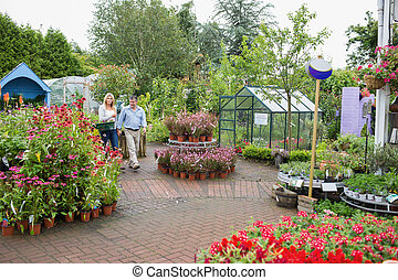 Garden center with couple walking through carrying basket...