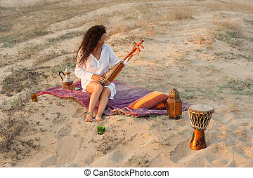 Woman wiht sitar - Woman with a sitar in a desert  setting
