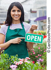 Woman holding an open sign - garden center employee holding...