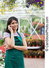 Florist doing a phone call while smiling and standing in the...