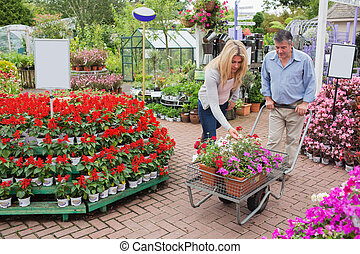 Customers pushing trolley through garden center - Customers...