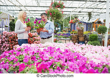Couple choosing flowers in the garden centre while talking