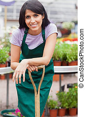 Woman leaning on shovel in garden center - Woman working in...