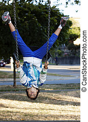 girl upside down on swing at park