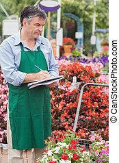 Man doing stocktaking in garden center