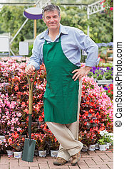 Man leaning on a spade while smiling in garden center