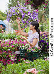 Woman shopping for flowers in garden center carrying basket