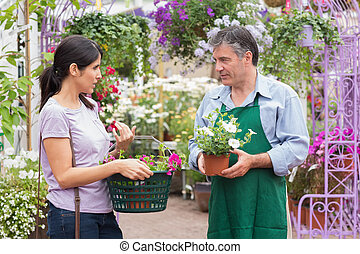 Customer talking to garden center worker about potted plants