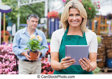 Smiling woman holding a tablet pc with customer holding...