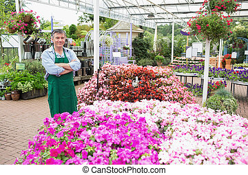 Employee in garden center - Smiling employee in garden...