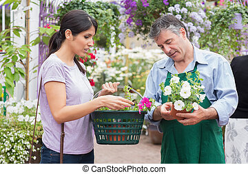 Woman carrying a basket while buying flowers in the garden...