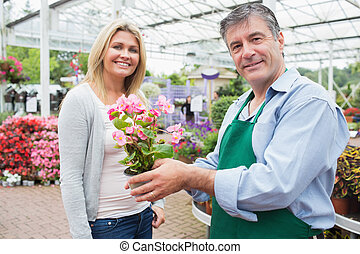 Garden center worker holding plant standing with woman -...