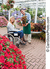 Smiling woman in wheelchair buying a flower