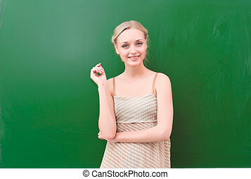 teacher near blackboard - beautiful young teacher is...
