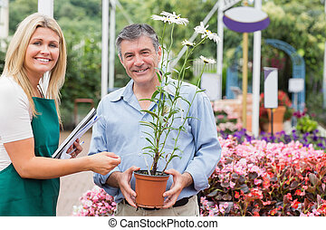 Gardener giving advice to customer while holding a flower...