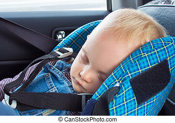 Little baby sleeping in a car seat strapped in the car