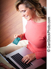 Woman with laptop and a credit card.