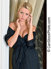 Beautiful woman in black silk robe with naked shoulders. -...