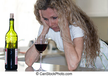 depressed house wife - Depressed woman, drinking wine in...