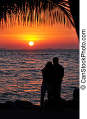 Sunset Romance - Silhouette of a romantic young couple...