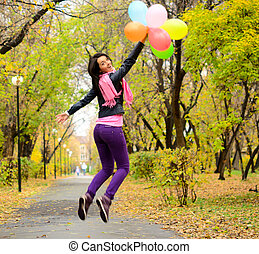 jumping woman with balloons in an autumn park