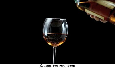pouring wine - Stem glass of amber amber wine over black...