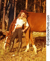Young cowgirl with her red horse at sunset.