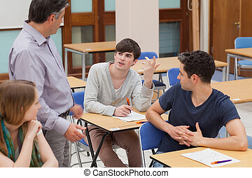 Students sitting talking to the teacher
