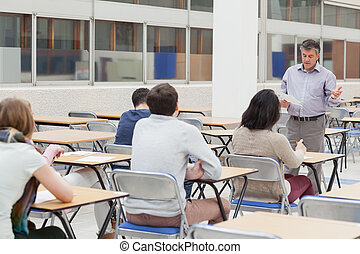 Lecturer talking at top of class in college