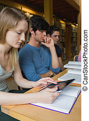 Woman in study group using tablet pc at desk in college...