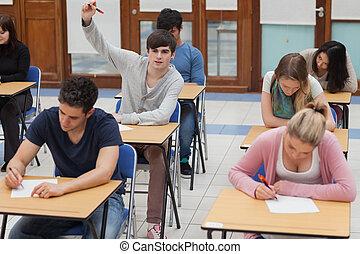 Boy raising hand during exam - Student raising hand during...