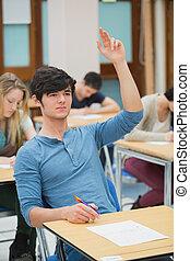 Student raising hand during exam - Student raising hand to...
