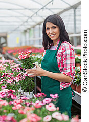 Worker holding a flower and smiling - Woman holding a flower...