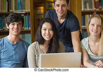 Students sitting at the library while smiling with a laptop