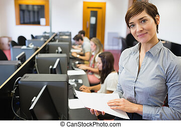Teacher standing at the computer room holding papers in...