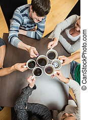 People holding up cups of coffee - Students sitting holding...