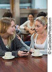Student comforting upset friend with mobile phone in college...