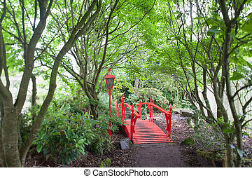 Red Japanese style bridge in forest - Red Japanese style...